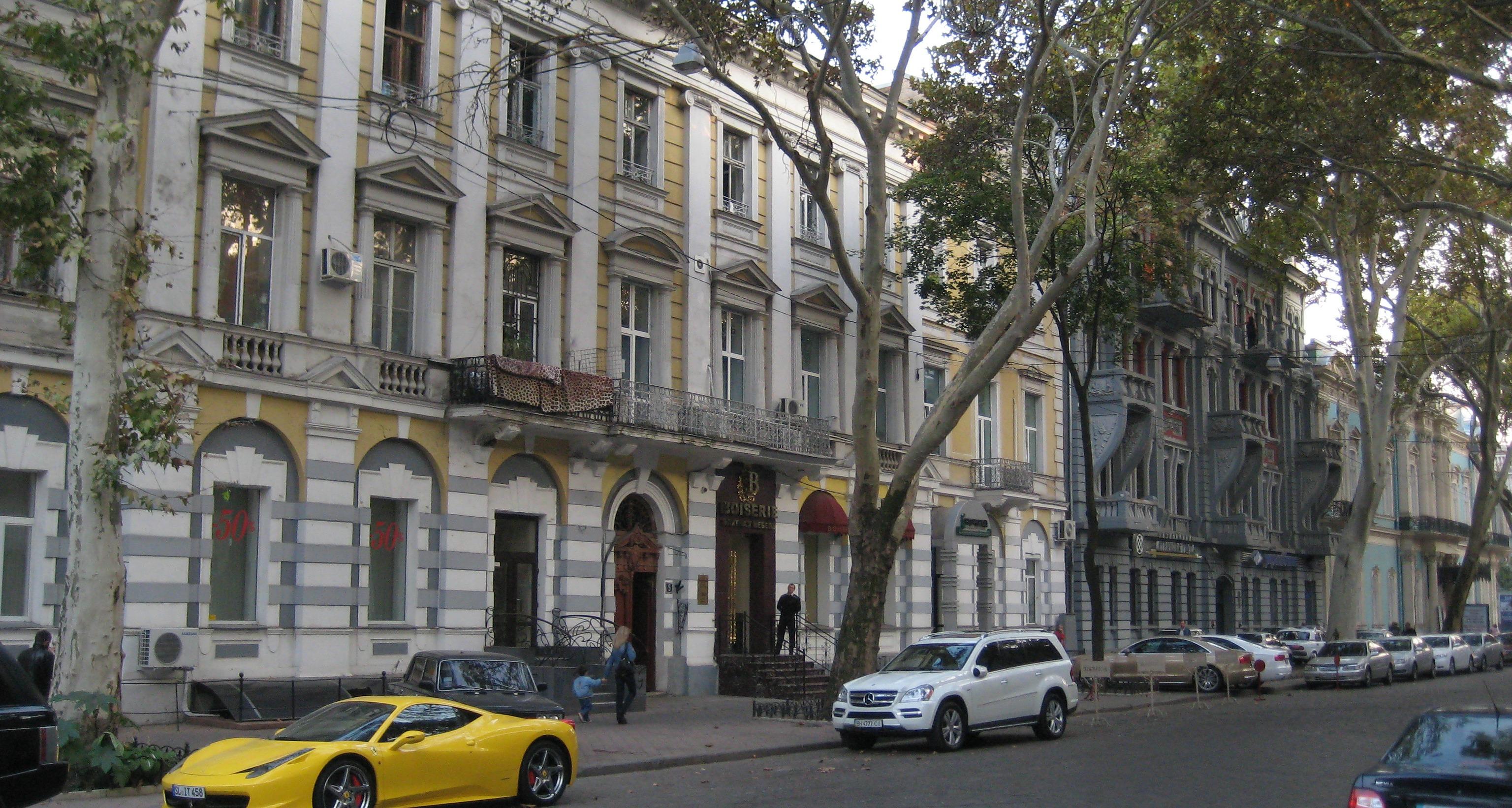 Fancy cars on a tree lined street in Odessa.